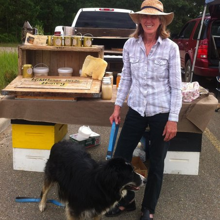 Image of Hudson the sheep dog and Sara at the farmer's market